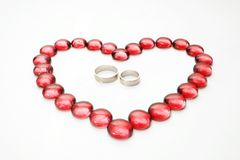 Glass Pebbles And Wedding Rings Royalty Free Stock Photography