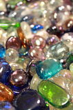 Glass pebbles. Shiny pebbles of varying colors reflect light around them Stock Images