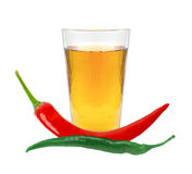 Glass of pepper vodka and chili peppers isolated on white Royalty Free Stock Images