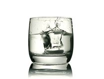 Glass with a piece of ice. Glass with a splashing piece of ice, clipping path is included Stock Photo