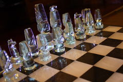 Glass pieces on chessboard. Glass pieces arranged at start of game on marble chessboard Stock Image