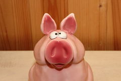 Glass pig, piggy bank. On a wooden background Royalty Free Stock Photo