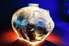 Glass piggy bank. On a colorful background Stock Photos