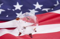 Glass Piggy bank against American national flag Stock Image