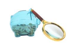 Glass Piggy bank with coins and magnifying glass. On white royalty free stock images