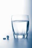 glass pillsvatten för huvudvärkstablett Royaltyfri Foto