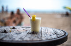 Glass of pinacolada on the table on the beach Stock Photography
