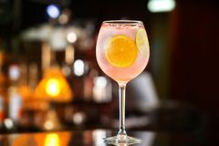 Glass of pink alcohol cocktail decorated with lemon slices at ba. R counter background royalty free stock image