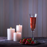Glass of pink champagne and strawberries on a wooden table Stock Photos