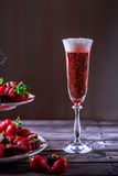 Glass of pink champagne on a wooden table. Stand with strawberri Stock Photography