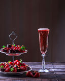 Glass of pink champagne on a wooden table. Stand with strawberri Stock Photo