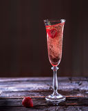 Glass of pink champagne on a wooden table. Strawberries into gla Royalty Free Stock Image