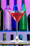 Glass with pink cocktail on centre of bar table. With green and blue bottles on background lighted with violet color Stock Image