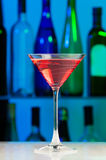 Glass with pink cocktail on table of bar Stock Photography
