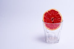 A glass of pink grapefruit on white background. A glass of pink grapefruit on a white background Royalty Free Stock Image