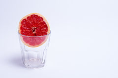 A glass of pink grapefruit on white background. A glass of pink grapefruit on a white background Stock Photo