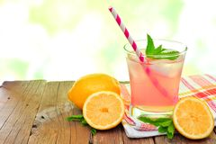 Glass of pink lemonade with mint and outdoors background. Glass of cold pink lemonade with lemon slices and mint, on wood with outdoors background Royalty Free Stock Photo