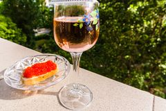 A glass of pink wine and bread with red caviar on the parapet. Wineglass with pink wine and bread with red caviar on the parapet on the background of city, hand royalty free stock photography