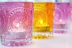 Glass pink and yellow candlesticks on light windowsill background Royalty Free Stock Image