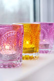 Glass pink and yellow candlesticks on white windowsill Royalty Free Stock Photos