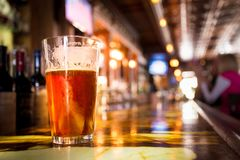 Glass Pint of amber beer with colorful blur of bar. In background royalty free stock photos