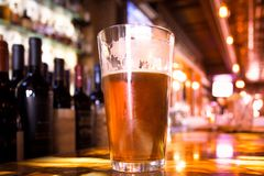 Glass Pint of amber beer with colorful blur of bar royalty free stock photos