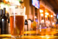 Glass Pint of amber beer with colorful blur of bar royalty free stock image