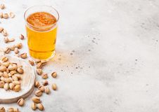Glass pint of craft lager beer with pistachio nuts on stone kitchen table background. Beer and snack. Space for text stock photo