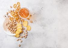 Glass pint of craft lager beer with snack on stone kitchen table background. Pretzel and crisps and pistachio on roud wooden board stock photos