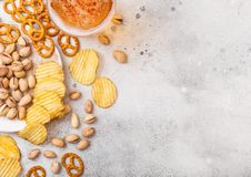 Glass pint of craft lager beer with snack on stone kitchen table background. Pretzel and crisps and pistachio on roud wooden board stock image