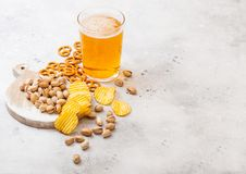Glass pint of craft lager beer with snack on stone kitchen table background. Pretzel and crisps and pistachio on roud wooden board stock images