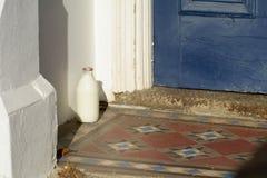 Glass pint milk bottle outside house Royalty Free Stock Photo