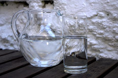 Glass and pitcher. Filled by water Royalty Free Stock Photos