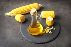 Glass pitcher with corn oil and cobs on background. Glass pitcher with corn oil and cobs on grey background Stock Photo