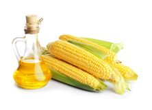 Glass pitcher with corn oil and ripe cobs. On white background Stock Photo