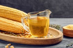 Glass pitcher with corn oil. On wooden tray Stock Photos