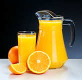 Glass and pitcher of fresh orange juice Royalty Free Stock Photos