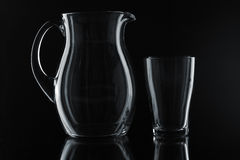 Glass pitcher and glass. On a black background Royalty Free Stock Images