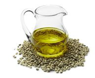 Glass pitcher with hemp oil. On white Stock Photography