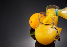 Glass pitcher and orange juice on black Royalty Free Stock Photography