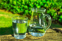 Glass and pitcher with pure water on wooden log, green grass, trees in the background, bright sunny day Royalty Free Stock Photography