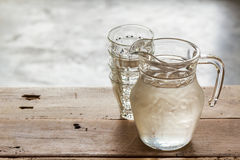 Glass pitcher of water and glass. Glass pitcher of water and glass on wooden table background royalty free stock photography