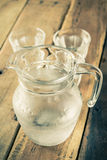 Glass pitcher of water and glass on wooden table. Stock Image