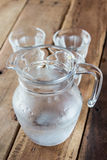 Glass pitcher of water and glass on wooden table. Royalty Free Stock Photos