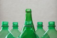 Glass and Plastic Bottles. A glass bottle surmounts plastic bottles, grey background royalty free stock photos