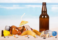 Glass and plastic bottles, food waste in  sand against sea. Royalty Free Stock Photo