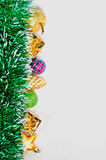 Glass and plastic Christmas toys and green tinsel bright garland isolated on white background. Stock Photos