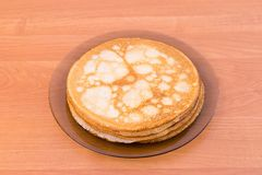 Russian pancakes blini. A glass plate of blini - traditional russian pancakes on the wooden table, top view royalty free stock image