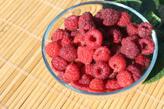 Glass plate with fresh ripe raspberry standing on a table Stock Images