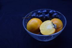 An glass plate with fruits. A transparent glass plate with black grapes, orange mandarins and a half of persimmon Stock Photo